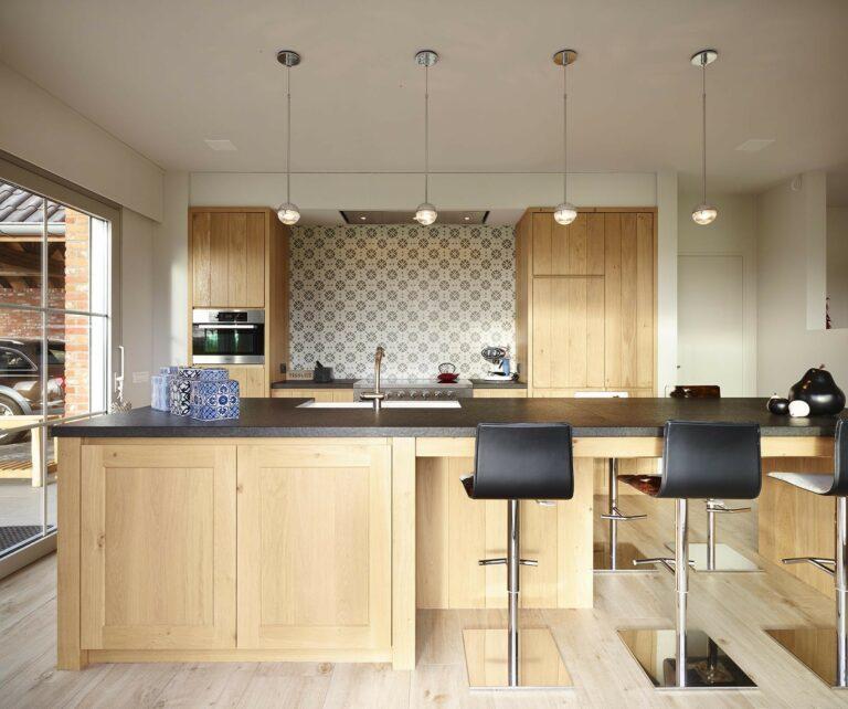 Vooraanzicht houten keuken met barstoelen