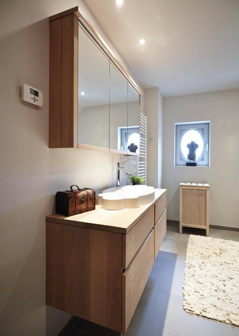Zijaanzicht van houten badkamer met ruime spiegelkast