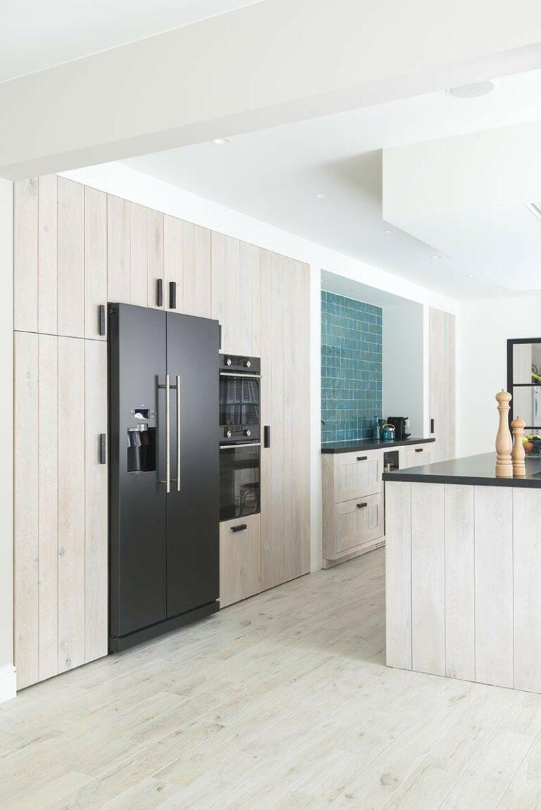 Zijaanzicht lichte open keuken met kookeiland