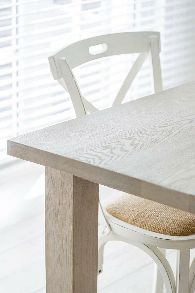 Houten eettafel met witte klassieke stoelen