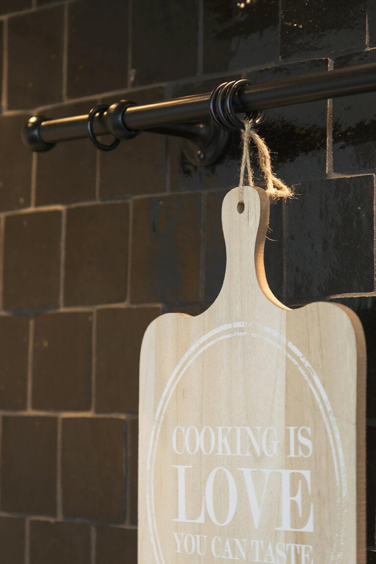 Zwarte keukenmuur met ophangsysteem voor snijplank