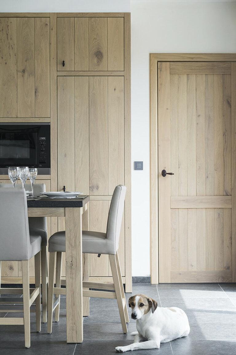 Hoge houten keukentafel met grijs beklede barstoelen