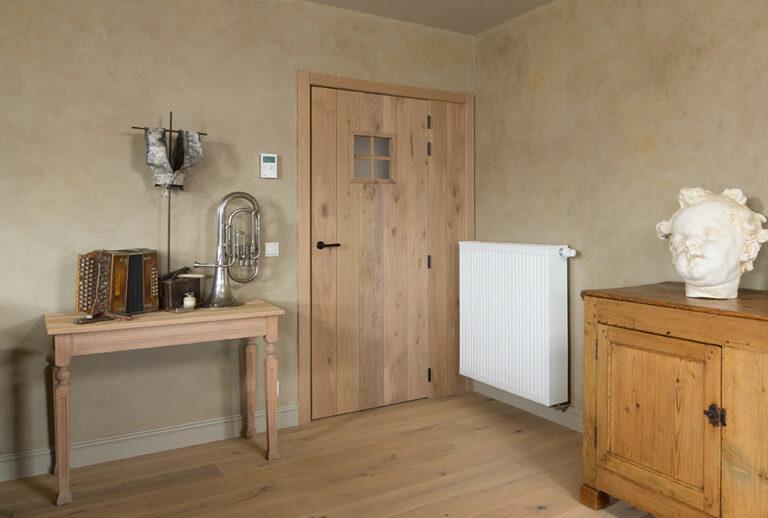 Eikenhouten deur naast verwarmingstoestel