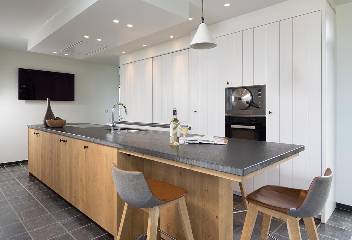 Massief houten kookeiland met witte houten keukenmuur