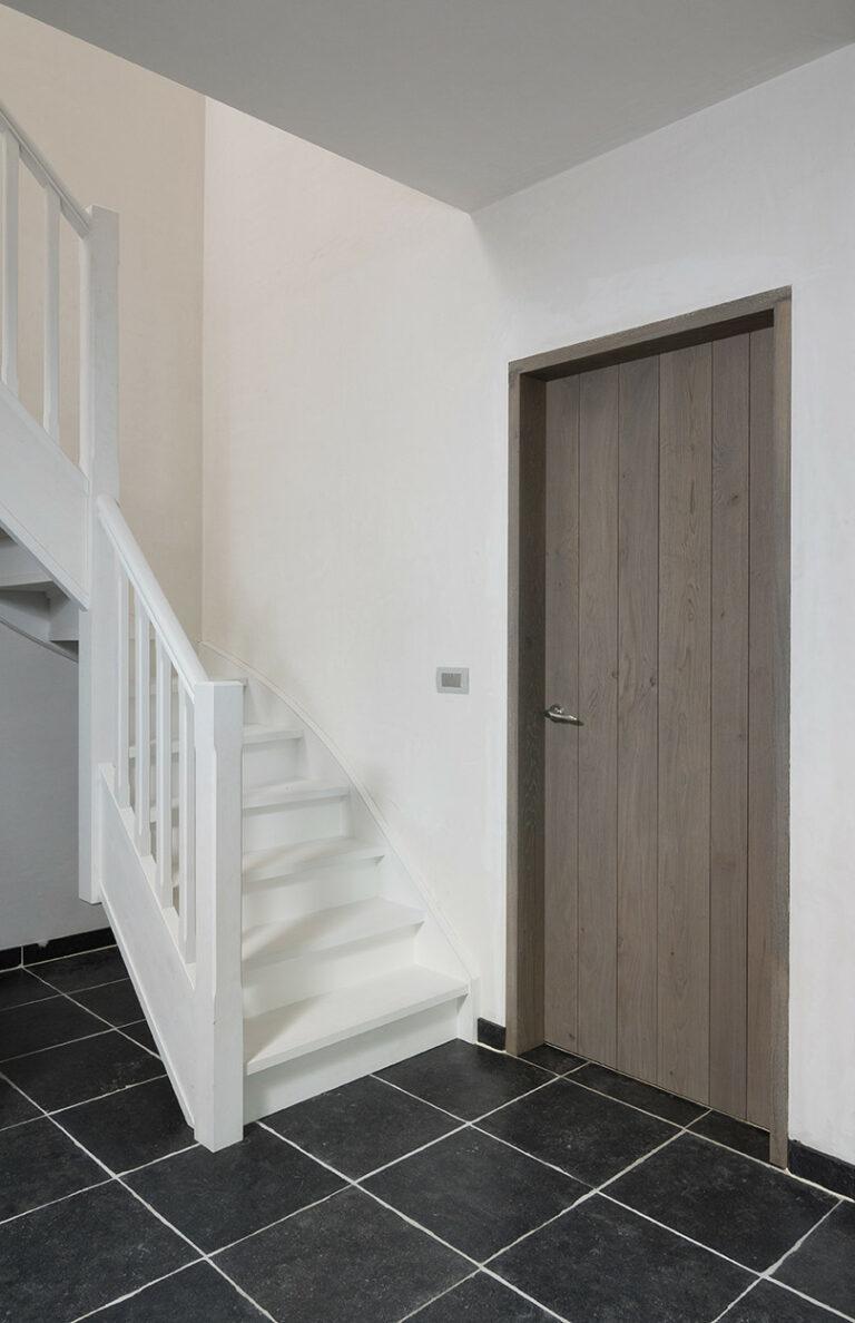 Donkere houten binnendeur met witte trap