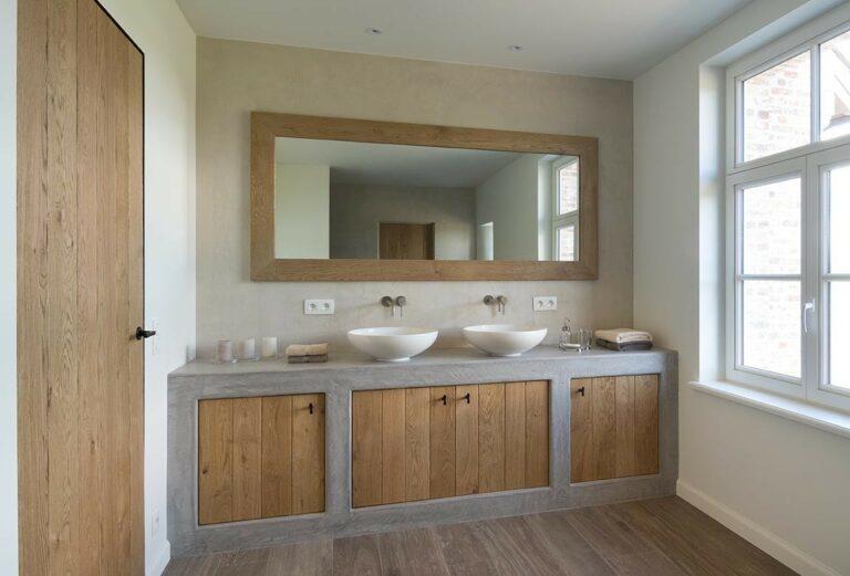 Badkamer met grote spiegel met eikenhouten randen