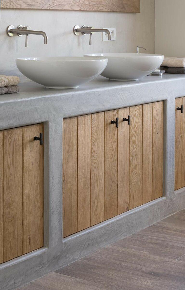 Betonkleurige badkamermeubelen met houten deurtjes