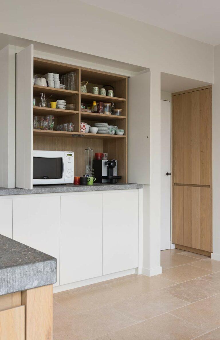 Verborgen houten keukenkast met ontbijtservies