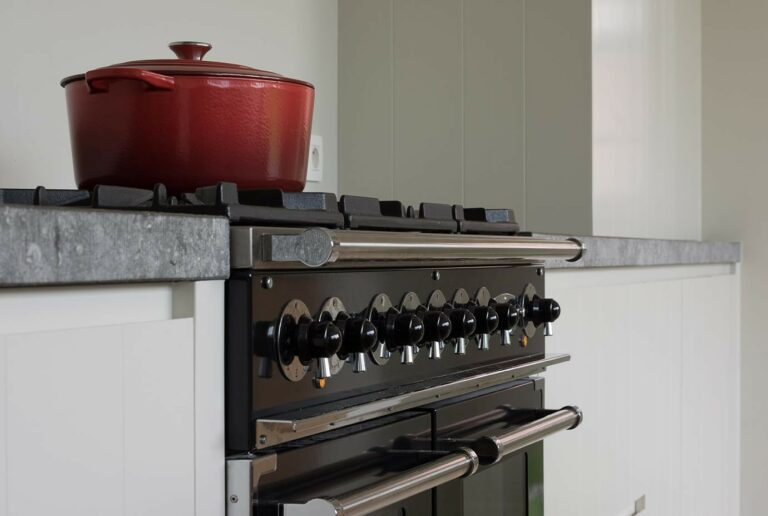 Klassiek gasfornuis in witte houten keuken