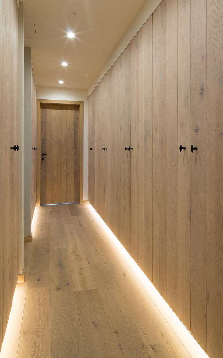 Gang met ruime houten inbouwkasten