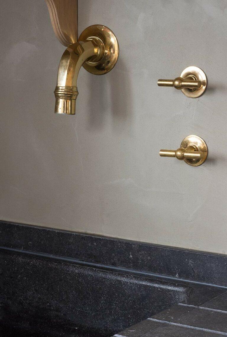 Goudkleurig kraanwerk in gebroken grijze muur