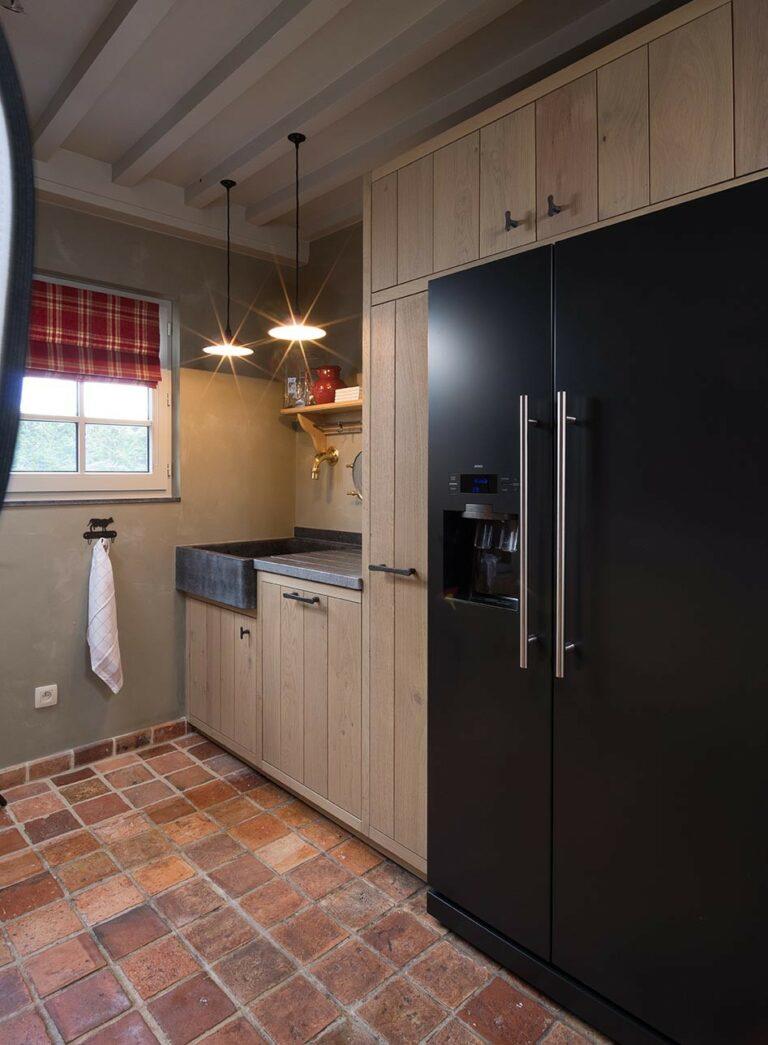 Keuken in warme kleuren gecombineerd met zwarte koelkast